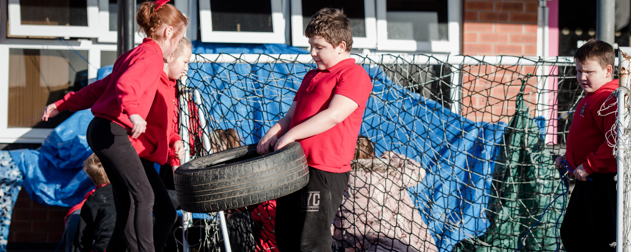Children playing with tyres in school playground