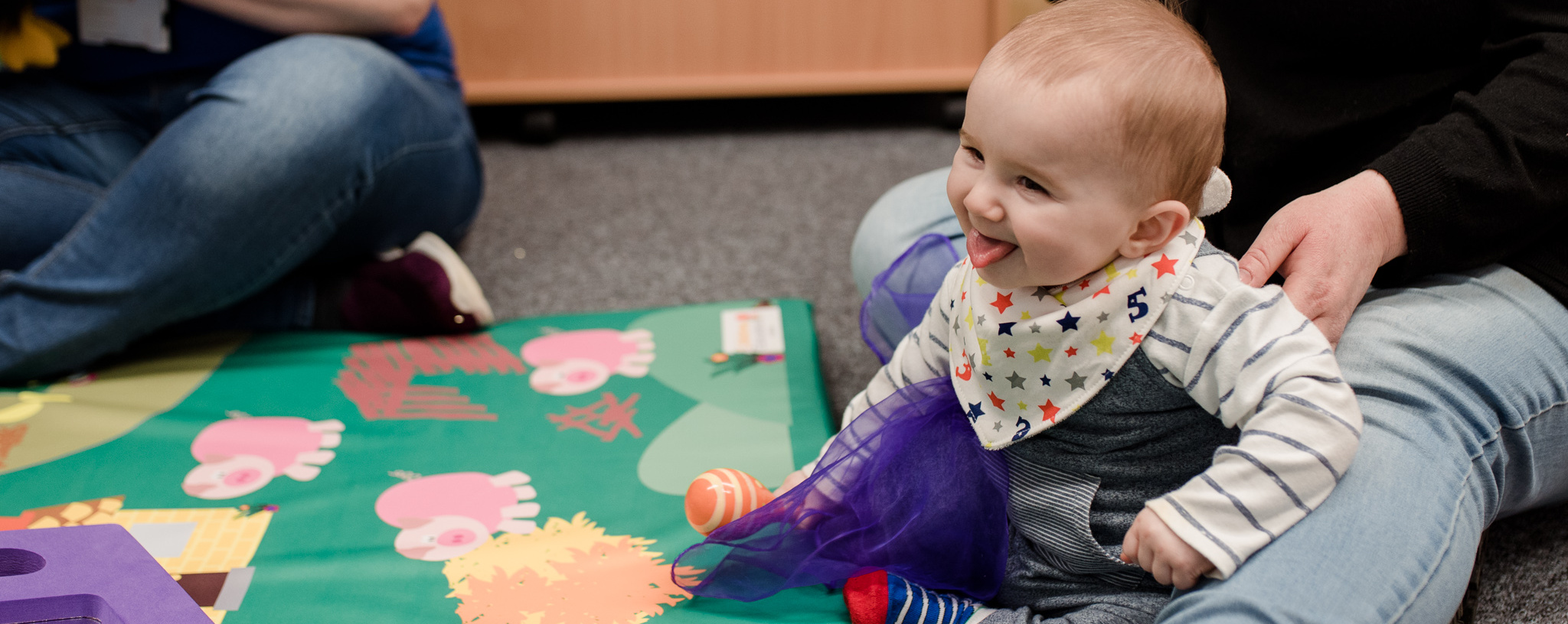 Baby smiling playing with rattle