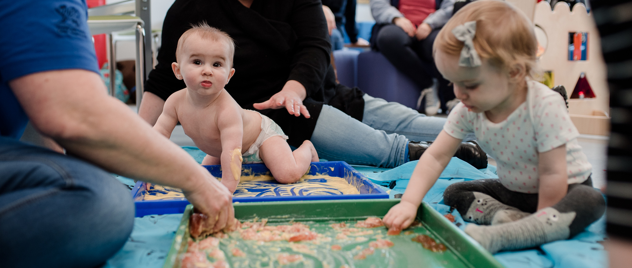 Baby and toddler playing in sand tray