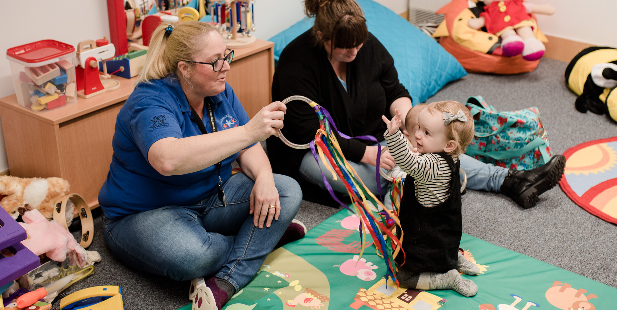 Carers playing with coloured ribbons and toddler