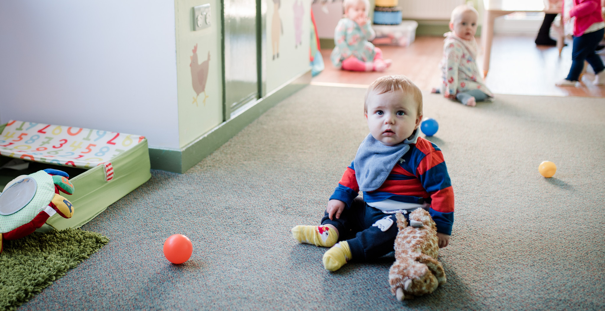 Babies playing with plastic balls on the floor
